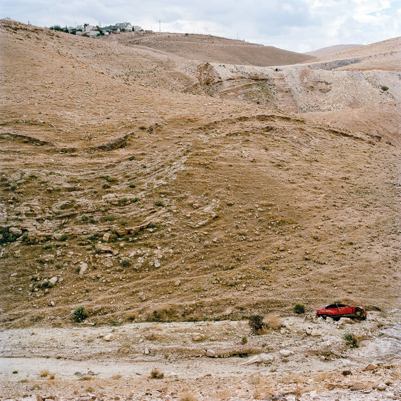 Wrecked car in Wadi Qelt, with an Israeli settlement hovering above.